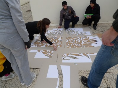Students and teachers work on a stencil in Sminthi 